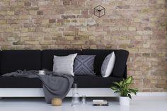 Salon, ściana z cegieł, ciemna kanapa, jasne poduszki, materiał we wzory. Zobacz więcej na: https://www.homify.pl/katalogi-inspiracji/12542/jak-dekorowac-wnetrze-poduszkami