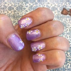 Spring lavender gel nails with daisy flower decor.