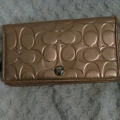 Metallic gold coach wallet This leather embossed wallet matches the f17727 east west gallery tote. Has a little bit of the gold that has transferred onto the brown id holder. One small pen mark on lavender lining as shown in picture. Otherwise great shape. Coach Bags Wallets