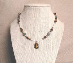 Gorgeous in gold!  This charming choker-length necklace was hand-crafted from ivory white glass, oodles of stunning gold-brown tiger's eye, pewter flower accents and silver-plated barrel fittings, then crowned with a gorgeous tiger's eye teardrop pendant set in sterling silver, courtesy of a Native American (Navajo) artisan.  Enjoy :)