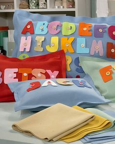 Alphabet Pillow  This easy-to-make pillow -- cleverly embellished with buttons and felt letters -- provides a perfect way to help toddlers develop their motor skills and learn how to spell their names.