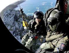 """Cliff winching with 771 Naval Air Squadron. Pictured- 771 NAS conducting cliff winching training off the coast of Cornwall. Royal Marine Corporal Aircrewman Justin Morgan and Leading aircrewman Sarah """"Chrissy"""" Christenson, are lowered on the winch line by Royal Navy Lieutenant Mark Thomas, to the cliff edge, 80 feet below the hovering Seaking MK 5 Aircraft. 771 Naval Air Squadron, based at Royal Naval Air Station Culdrose (HMS Seahawk), near Helston, Cornwall"""