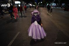 """A girl dressed as """"Catrina"""" walks while taking part in the """"Catrinas Parade"""" along Reforma Avenue, in Mexico City on October 23, 2016. Mexicans get ready to celebrate the Day of the Dead highlighting the character of La Catrina which was created by..."""