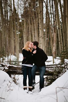 Snowy mountain engagement kiss.
