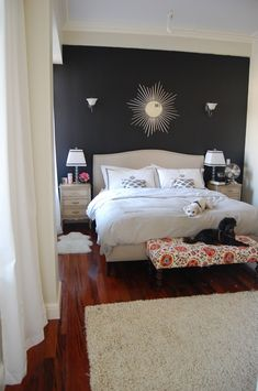 This accent wall is painted a dark grey with white furniture to be placed in front of it as to not overwhelm the room with such a dark color.