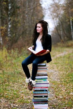 """books0977:  Sister reading on tower of books in forest. Photograph by Aks London. """"All the best stories in the world are but one story in reality — the story of escape. It is the only thing which interests us all and at all times, how to escape.""""  - Arthur Christopher Benson"""