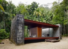 """This 2005 project by Carla Juacaba is a weekend home located in Rio de Janeiro, Brazil. It is a crudely elegant structure built to withstand the demands of its tropical environment while providing the owners with views of the nearby river.                   Rio Bonito House by Carla Juacaba: """"The mountain of Freiburg in the Hinterland of the Rio Bonito Lumiar, was the place chosen for the construction of the residence-retreat director of the museum of unconscious images. The proximity of the…"""