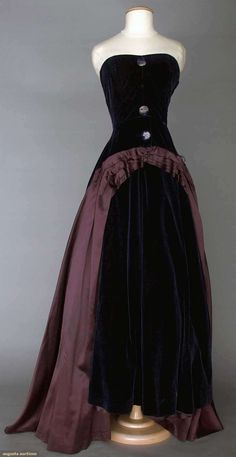 "SCHIAPARELLI COUTURE GOWN, c. 1940 Midnight blue velvet w/ plum rayon side panels, strapless, boned & fitted bodice, wide bell-shaped skirt, 4 CF irridescent blue glass buttons w/ stylized black center cross, (1 button missing), labeled ""Schiaparelli, 21 place vendome, Paris"", label tape ""44611"", dark blue bodice lining, ivory buckram skirt lining."