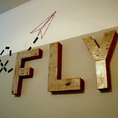 FLY letters and paper airplane painted and wall and trail with electrical tape