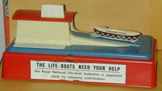 """Mechanical charity collection money box from my personal collection.  When a coin is placed in the roof, the boat rolls down the ramp.  Distributed in the UK to stores and collected on a regular basis.  The mechanical versions are quite rare.  After collection, they were """"resealed"""" with a paper sticker."""