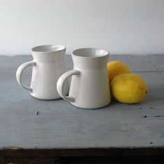 White Bennington Mugs: An interesting set of white mugs in a modern primitive style of Bennington Pottery. The irregular handcrafted features make these otherwise plain white mugs stand out. Bennington Pottery was founded by David Gil in the 1960's in Bennington, Vermont. $41 for pair.
