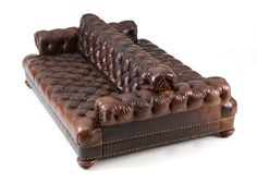 A double chesterfield style sofa, having a deep button-tufted, double-back section, which fits between rolled arms and a wide seat, designed for back-to-back seating. The brown leather has an aged . Chesterfield Style Sofa, Barbershop Design, Royal Furniture, Patterned Armchair, Accent Chairs For Living Room, Cool Chairs, Arm Chairs, Back Seat, Tufting Buttons
