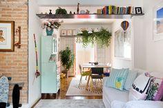 Integração da sala de estar e jantar. Detalhe para prateleira alta com plantas pendentes.