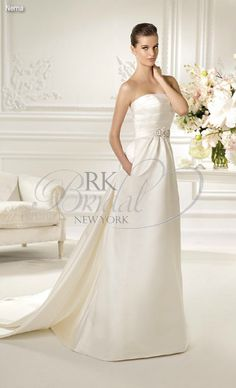 RK Bridal in NYC: White One Spring 2013 - Nema  A division of Pronovias. Strapless Royal satin a-line gown with grosgrain applications and silver and white beading. Shown with beaded embroidery tulle veil style V-2732, sold separately.