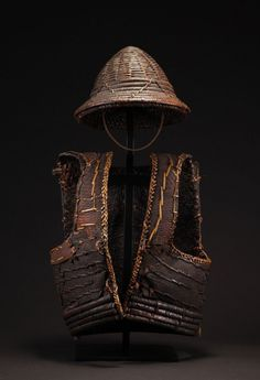 """Virtual Artifacts Armour and Helmet Set Yami peoples of Orchid Island, Taiwan Rattan and fish leather 32"""" tall by 17.5"""" wide 19th century with some early 20th century indigenous restoration Hardened fish leather with a dark smoky patina. The light color leather and yellow rattan are later indigenous restorations to keep the armour in use."""
