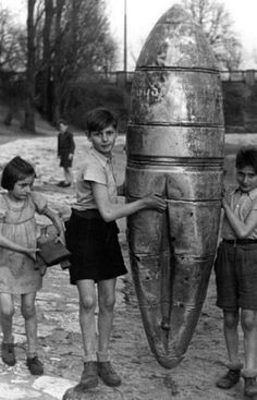 Children play with the shell of a dropped bomb. Berlin, WWII.