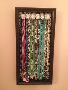 I made this to organize my necklaces.  You need:  * Shadow box frame  * wooden pegs  * drill  * hot glue gun  * gift wrap of your choosing  decorations for the pegs. I chose cloth flowers.  * & hung with sticky wall strips.