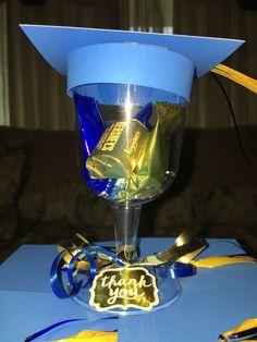 I made these cute adorable favors for my daughter's high school graduation party. I bought blue and gold candies to go inside the cup to match the school colors which was a nice touch. I hot glued down some ribbon to the top of the cup to make a tassel for the cap. For the hat I measured the rim of the cup and cut out a strip of paper and for the top I just cut a square that was just a bit bigger than the opening of the cup. I then taped the strip and square together creating a cap.