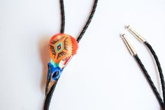 This is a real magpie bird skull hand-painted with original design by Carmadilla. Inspired by Southwest colors and Native American designs. Lovely with pearl snap, scoop neck, dress or denim. Great for special occasions or any occasion for showing off a unique piece of art around your neck. A certified conversation piece. Southwest colors - orange, yellow, turquoise, blue with a hint of red and metallic. On a 42 black leather cord with a silver slide and tips. Very fragile - these bones are…
