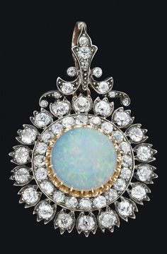 *A Victorian opal and diamond cluster pendant by West & Son, Dublin, The central round white opal cabochon of estimated weight carats in a stepped surround of old brilliant cut diamonds of estimated total weight carats. Victorian Jewelry, Antique Jewelry, Vintage Jewelry, Victorian Era, Handmade Jewelry, Opal Jewelry, Fine Jewelry, Jewellery, Wedding Jewelry