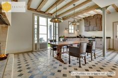 Rustic French kitchen with original tiles and wooden beams with modern, industrial touches. In a #luxury Pure France holiday rental château, ref. 37003. www.purefrance.com
