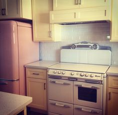O'keefe & Merritt stove in retro inspired buy new kitchen. Yellow cabinets, white stove, pink Northstar fridge