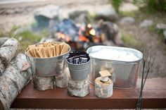 smore fixings in tin cans on logs of wood.