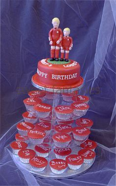 Round Birthday Cake covered with Red Icing and topped with 2 hand made sugar paste figures dressed in the Liverpool Strip. Cupcakes covered with red icing and topped with names.