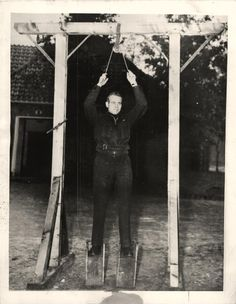 1944- RCAF soldier stands on gallows found at German concentration camp in Vught, Holland.