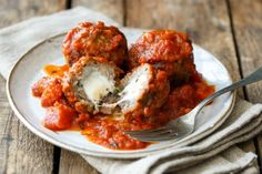 Extra-large, extra-flavorful meatball recipe stuffed with melty mozzarella cheese and simmered in a chunky, spicy tomato sauce. How To Cook Meatballs, Italian Meatballs, Cheesy Meatballs, Meatball Recipes, Meat Recipes, Cooking Recipes, Dinner Recipes, Dinner Ideas, Bread And Company