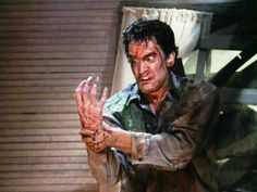 """""""Evil Dead II"""", (aka: Evil Dead 2: Dead by Dawn), directed by Sam Raimi. Seen here, Bruce Campbell as Ash struggling with his demon possessed hand. Initial theatrical release, March 13, 1987. Screen capture. Copyright © 1987 Rosebud Releasing Corporation"""