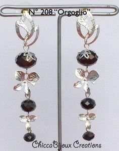 ORGOGLIO Orecchini composti da perni color argento a 3 foglie traforate, cristalli, fiori color argento. € 10.00