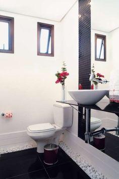 Rodapés altos e imponentes , pastilhas de vidro, espelho de corpo inteiro refletindo o clássico branco e preto compinceladas em vermelho. Emoldurando o piso, seixos brancos.