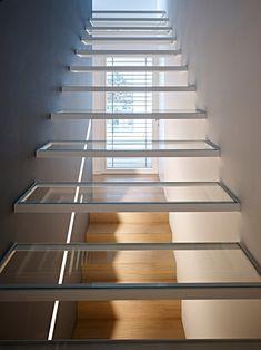 Eccellente idea di scale moderne, semplici ma di grande impatto visivo. Gradini in vetro temperato all'interno di una cornice in metallo verniciato bianco