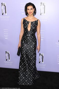 Utterly spellbinding: Holding a black clutch to her side, she tucked her cropped hair behind one ear, allowing for a glimpse at one of her white teardrop earrings