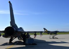 An F-16 Fighting Falcon taxis for takeoff, while crew chiefs conduct maintenance on another F-16, Sept. 24, 2014, at Lask Air Base, Poland. Seven F-16s and approximately 150 support Airmen from the 31st Fighter Wing at Aviano Air Base, Italy, are supporting the Polish AvDet rotation 14-4. (U.S. Air Force Photo/Tech. Sgt Eric Donner)
