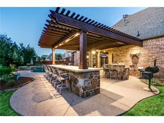 Outdoor kitchen and dining area with an arbor