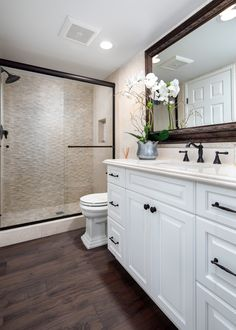 Hall bathroom remodel with Quartz countertops, white raised-panel vanity, pebble tile shower floor, porcelain wood tile flooring and oil rubbed bronze hardware & fixtures.