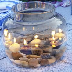 Fill goldfish bowls with water, riverstones and floating candles for natural light...