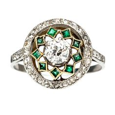 Swan Lake is an intricately designed antique Edwardian era ring made from platinum and 18kt yellow gold. This whimsical circular designed ring centers an six-prong set old European cut diamond weighing approximately 0.35ct graded H-I color and SI1 clarity enhanced by a halo of yellow gold bezel set square cut emeralds and further bordered by thirty single and rose diamonds