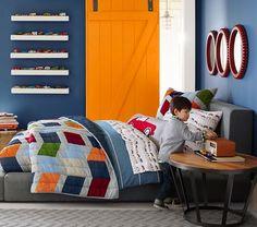peinture murale bleue, porte orange et literie multicolore dans la chambre de petit garçon