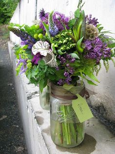 Purple and greens floral arrangement full of exotic flowers.