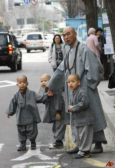 Novice Buddhist monks and their teacher wait to take a taxi in downtown Seoul, South Korea