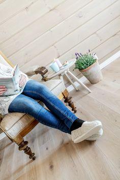 La roen senke seg med en bok og en kopp kaffe i godstolen. Rundtømmerpanel og heltregulv i Eik fra RingAlm. Skinny Jeans
