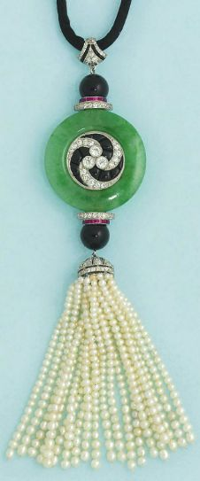 An early 20th century jadeite, onyx, ruby and diamond-set necklace  The circular polished jade plaque with swirling diamond and onyx central detail, between diamond, onyx and ruby terminals, to a seed pearl tassel terminal with diamond-set cap, to a silk necklace with diamond-set clasp, circa 1910