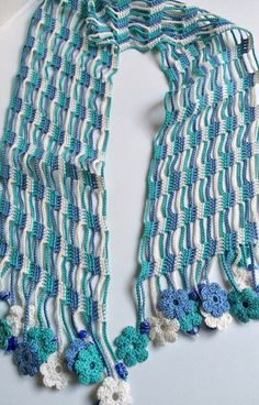 This light and beautiful summer scarf was made in crochet with cotton thread. The ends are composed by neatly pretty crochet flower motifs and blue ceramic beads. The blue shades effect is brightly gorgeous. Material: 100% cotton thread, ceramic beads . All my scarves are unique in the way that I never repeat the same colour pattern, and always make something new and different, even slightly, so we may say it is one of a kind.