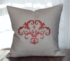 A hand painted/stenciled linen pillow cover, the emblem painted in a beautiful berry color with a mineral paint overlay for a soft shimmer