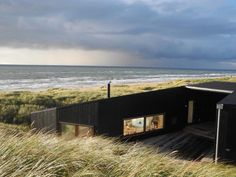 Danish practice Mette Lange Architects have designed a vacation home in Henne, Denmark. The small vacation house is located in the big dunes next to the Northern Sea on the Danish west coast. Beautiful Architecture, Beautiful Buildings, Architecture Details, Modern Architecture, Scandinavian Architecture, Porches, House By The Sea, Cabins In The Woods, Prefab