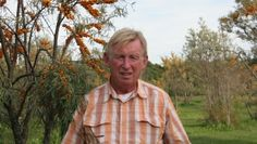 Roger Shankland in front of sea buckthorn trees