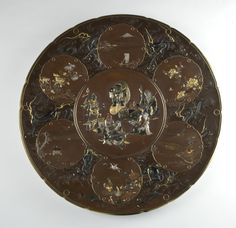 Inoue Company A superb inlaid bronze charger with a central panel decorated with the Seven Gods of Good Fortune delicately worked in honzoga...